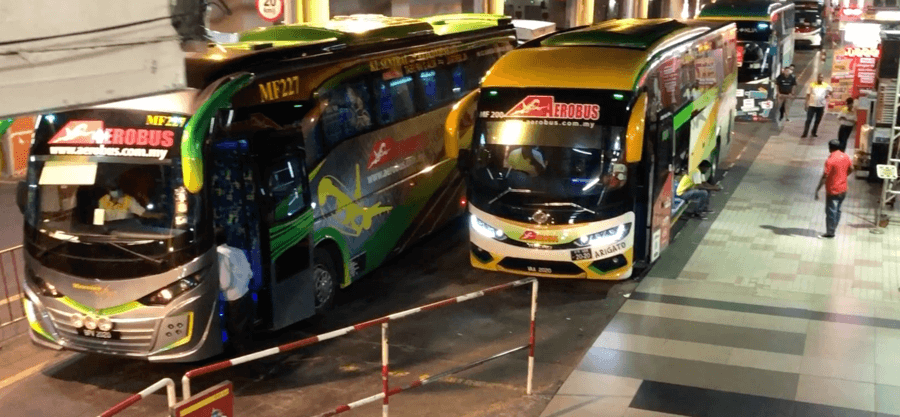 Several of the buses that travel between KL Sentral and KLIA shown parked at the bus station before departure to the airport.